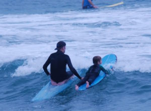 Rusty Miller teaching a young boy to surf at Byron Bay